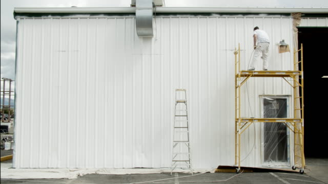 vídeos de stock e filmes b-roll de a caucasian professional painter in his thirties uses a paint sprayer to paint the outside of a metal warehouse while standing on a scaffold under partly cloudy sky - andaime
