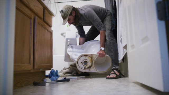 vídeos de stock e filmes b-roll de a caucasian repairman in his forties with a beard picks up a toilet resting on its side and sets it upright in an indoor domestic bathroom - domestic bathroom