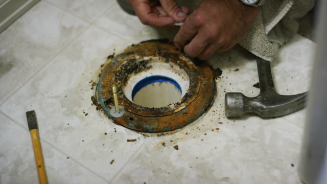 a caucasian repairman places new flange bolts and washer into a sewer flange underneath a removed toilet in an indoor domestic bathroom - broken pencil stock videos & royalty-free footage