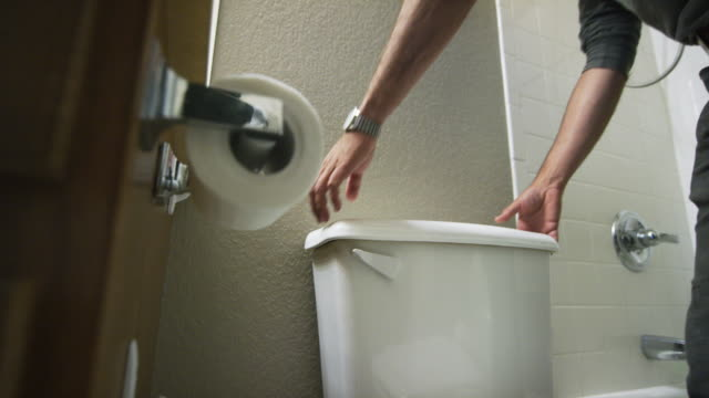a caucasian repairman removes a toilet tank cover and sets it on the lid of the toilet in an indoor domestic bathroom - plumber stock videos & royalty-free footage