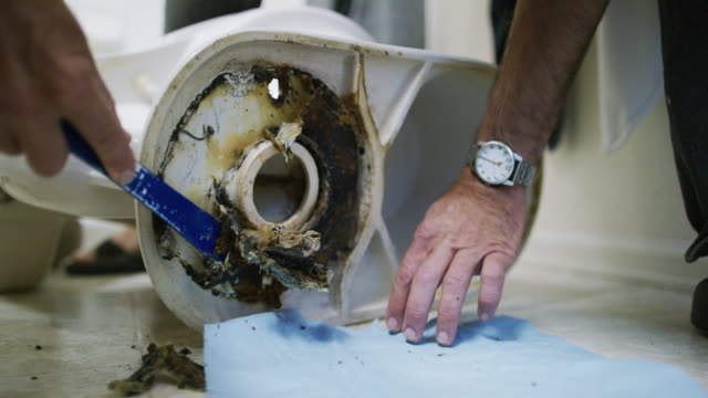 A Caucasian Repairman Uses a Paint Scraping Tool to Remove the Old Wax Ring from a Removed Toilet Sitting on Its Side Then Uses a Paper Towel to Clean the Paint Scraping Tool in an Indoor Domestic Bathroom