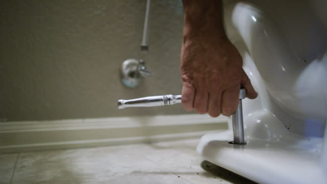 vídeos de stock e filmes b-roll de a caucasian repairman uses a socket wrench to ratchet the nut on to a toilet's flange bolt in an indoor domestic bathroom - domestic bathroom