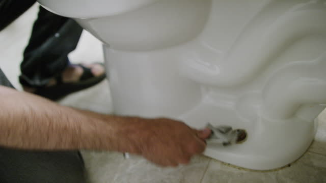 a caucasian repairman uses an adjustable wrench to loosen the nut bolting the toilet to the floor in an indoor domestic bathroom - bolt stock videos & royalty-free footage