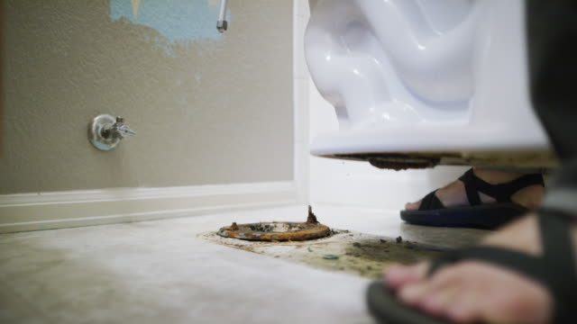 a caucasian repairman wearing sandals lift a porcelain toilet to reveal a dirty floor and wax ring underneath in an indoor domestic bathroom - under her feet stock videos & royalty-free footage