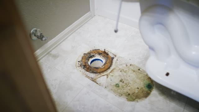 vídeos de stock, filmes e b-roll de as sandálias desgastando do reparador caucasiano levantam um toalete da porcelana para revelar um assoalho sujo e um anel da cera embaixo em um banheiro doméstico interno - ralo instalação doméstica