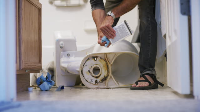 a caucasian repairman wearing sandals pours cleaning solvent onto a paper towel and wipes the remains of the old wax ring from underneath a removed toilet sitting on its side in an indoor domestic bathroom - wearing a towel stock videos & royalty-free footage