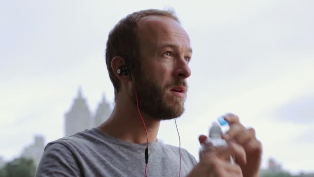 Caucasian runner drinking water bottle in Central Park, New York, New York, United States