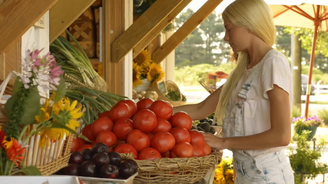 Caucasian seller arranging tomatoes at farm stand