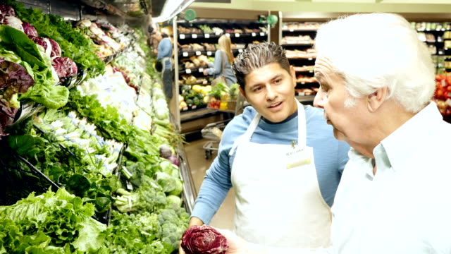 Caucasian senior adult man is getting advice about produce from mid-adult Hispanic male supermarket employee
