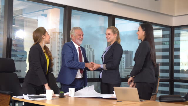 caucasian senior businessman discussing businesswoman and signing contracts and shaking hands for agreement deal togetherness in modern conference room - sign stock videos & royalty-free footage