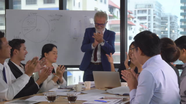 caucasian senior manager and asian businesspeople applauding for celebration to success work while meeting in modern workplace, pan shot - obedience stock videos & royalty-free footage