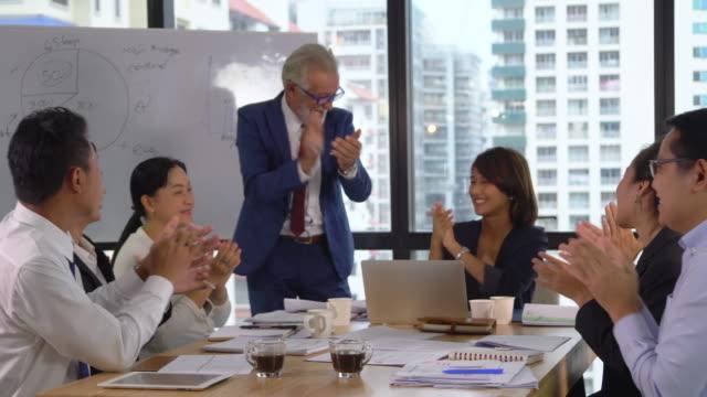 stockvideo's en b-roll-footage met kaukasische senior manager en aziatische zakenlieden juichen voor de viering van succes te werken, terwijl de vergadering in de moderne werkplek, pan shot - diavoorstelling