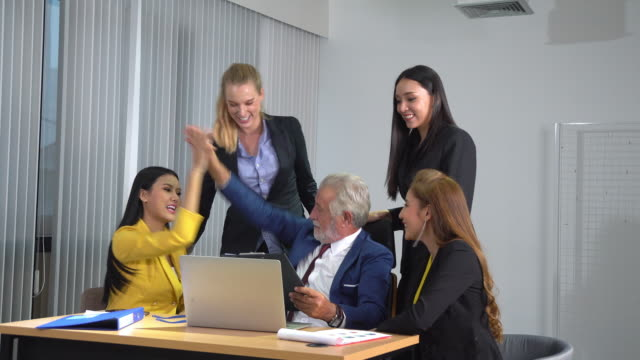 caucasian senior manager wearing suit with tie gives high five to businesswoman at his desk with laptop at high rise office - high up stock videos & royalty-free footage