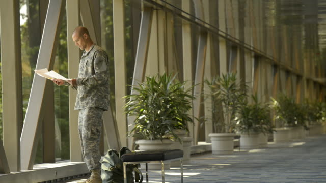 Caucasian soldier reading letter in airport