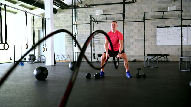 caucasian sportsman working out with battle ropes - rope stock videos & royalty-free footage