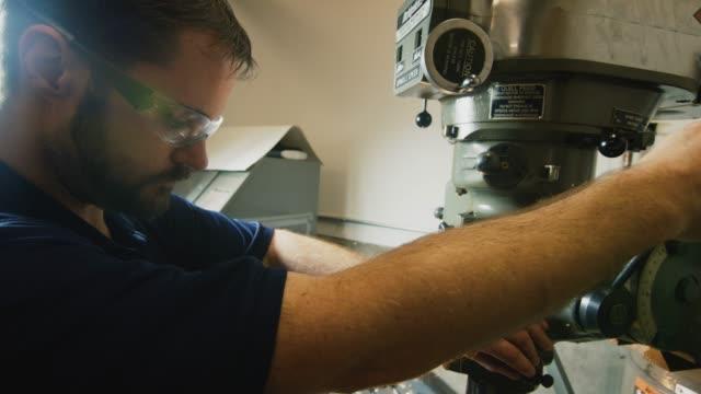 vídeos y material grabado en eventos de stock de un técnico caucásico en sus treinta prepara una fresadora vertical para su uso en una instalación de fabricación interior - un solo hombre de mediana edad