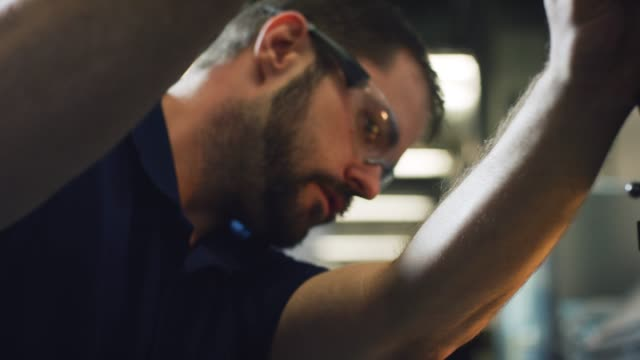 vídeos y material grabado en eventos de stock de un técnico caucásico en sus treinta prepara una fresadora vertical para su uso en una instalación de fabricación interior - cut video transition