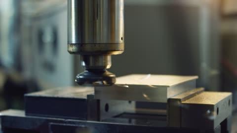 vídeos y material grabado en eventos de stock de un técnico caucásico en sus treinta utiliza una fresadora vertical para cortar a través de aluminio en una instalación de fabricación interior - aluminio