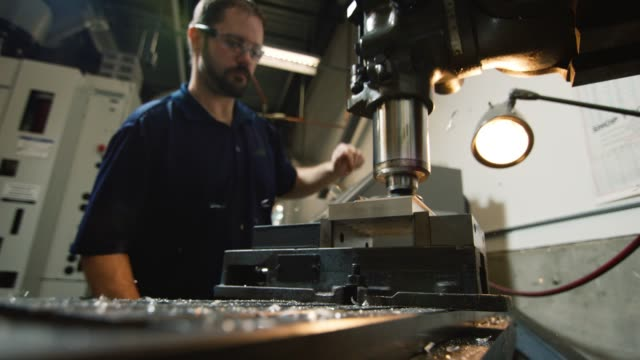 彼の30代の白人技術者は、金属破片が屋内製造施設で飛ぶように、垂直フライス盤を使用してアルミニウムを切断します - ドリルビット点の映像素材/bロール