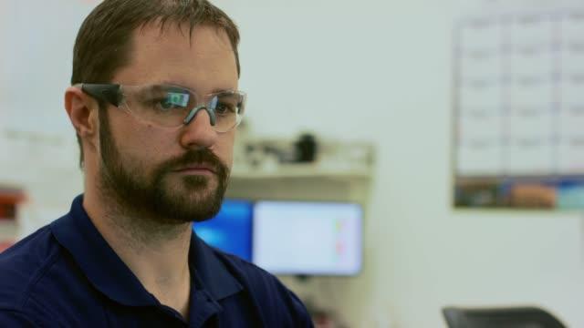 30代の白人技術者で、保護眼鏡を身に着けている屋内オフィスのコンピュータで働いている - 30代点の映像素材/bロール