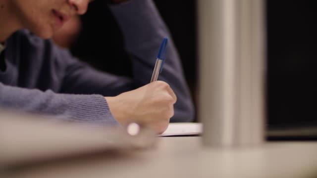 vidéos et rushes de teen caucasien écrit sur papier sur le bureau - concentration