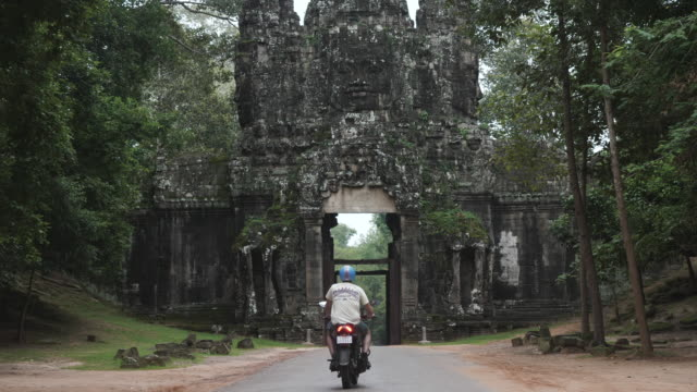 caucasian tourist riding a scooter through cambodian ruins - angkor wat stock videos and b-roll footage