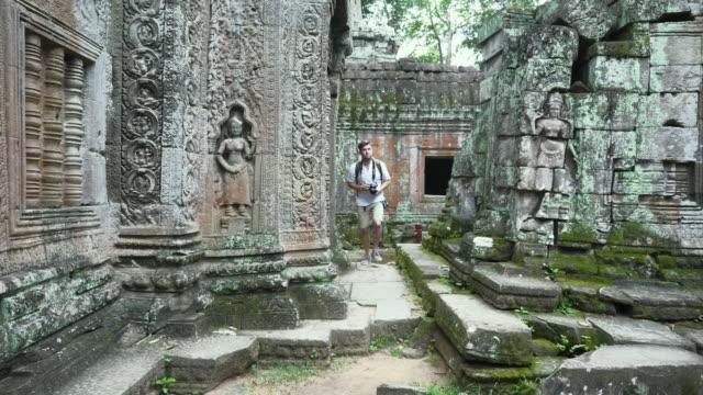 Caucasian Tourist Wandering through Cambodian Ruins