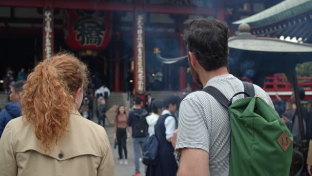 vídeos de stock e filmes b-roll de caucasian tourists walking towards temple of kannon - câmara à mão