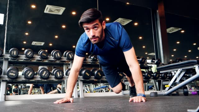 caucasian white with mustaches exercise at the gym by push-ups. there is a weight cube in the hand.healthy ,city life style concept. - bicep stock videos & royalty-free footage