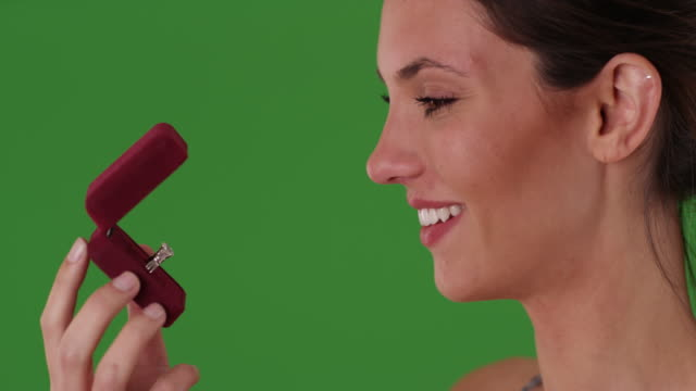 caucasian woman admiring diamond engagement ring in jewelry box on greenscreen - jewelry box stock videos and b-roll footage
