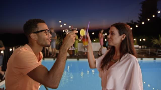 stockvideo's en b-roll-footage met kaukasische vrouw en multi-etnisch man met bril dansen bij het zwembad op een feestje in de avond - poolparty