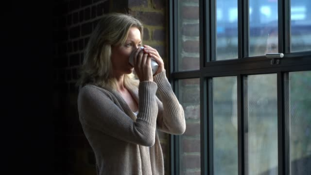 caucasian woman at home enjoying a cup of tea while looking out the window pensive - looking through window stock videos & royalty-free footage