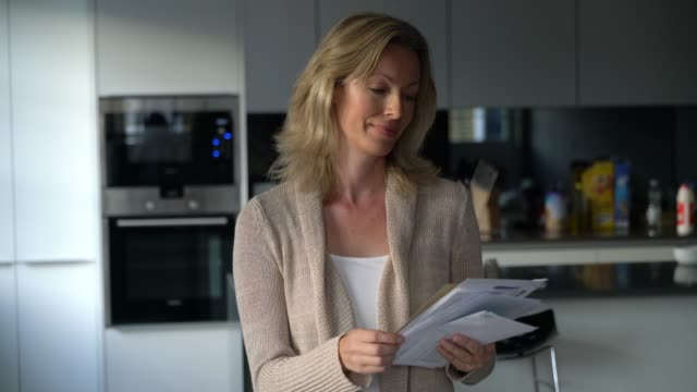caucasian woman at home going over her mail smiling - letterbox stock videos & royalty-free footage