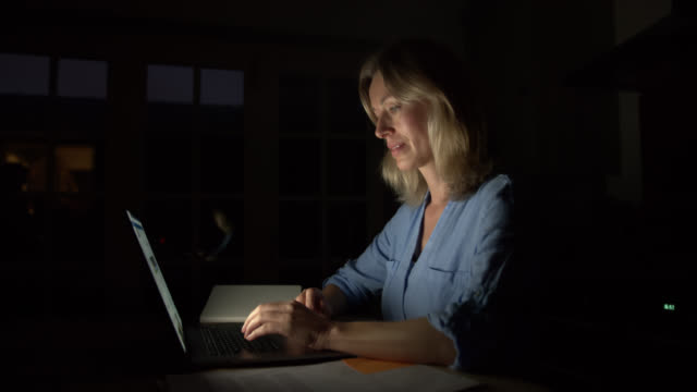 caucasian woman at home working late at night using her laptop - one mature woman only stock videos & royalty-free footage