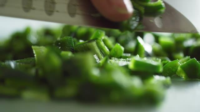 eine kaukasische frau schneidet einen poblano-pfeffer auf ein schneidebrett mit einem küchenmesser - küchenmesser stock-videos und b-roll-filmmaterial