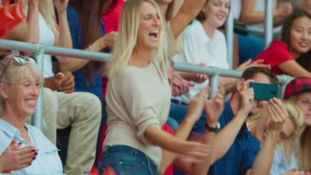 caucasian woman dancing on the stadium tribune at a sports event - competizione video stock e b–roll