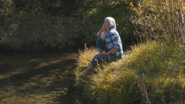 Caucasian woman dipping foot in river