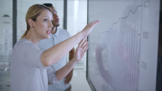 caucasian woman discussing a financial graph on the screen in meeting room with her african-american colleague - finanza video stock e b–roll