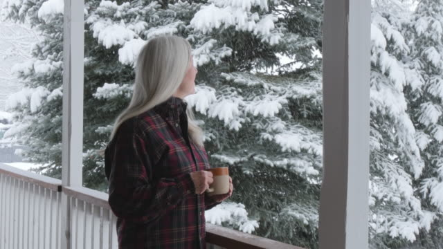 Caucasian woman drinking coffee on porch watching snow