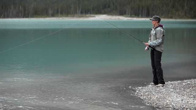 caucasian woman fishing on a mountain lake - cast member stock videos & royalty-free footage