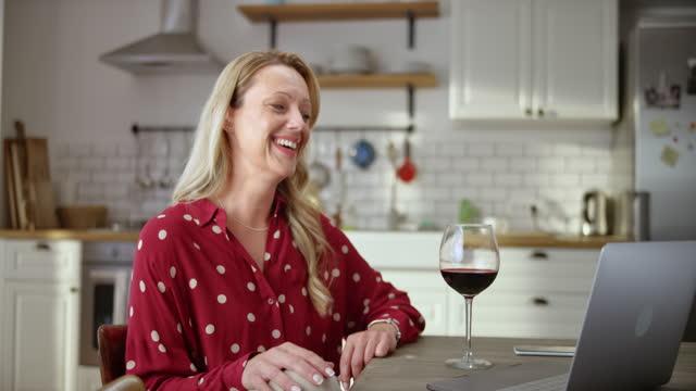 slo mo kaukasische frau mit einem glas wein zu hause während auf einem videoanruf - einzelne frau über 40 stock-videos und b-roll-filmmaterial