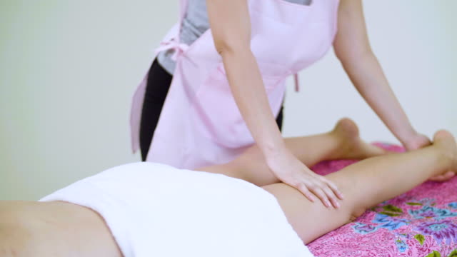 caucasian woman having leg massage by massage therapist on the massage bed in spa salon - reflexology stock videos and b-roll footage