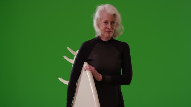 caucasian woman holding surfboard looking at camera confidently on greenscreen - old diving suit stock videos and b-roll footage