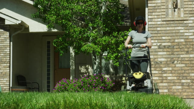 a caucasian woman in a caucasian woman in her thirties wearing a hat, sunglasses, hearing protec thirties wearing a hat, sunglasses, hearing protection, and gardening gloves uses a motorized lawn mower to mow the grass in front of her house on a sunny day - tosaerba video stock e b–roll