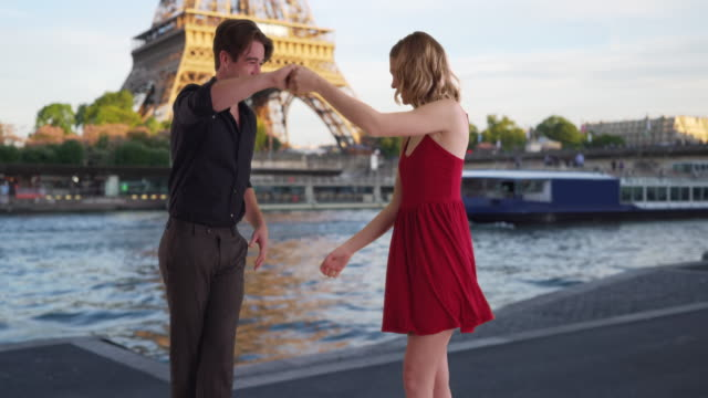 caucasian woman in a red dress dancing with her boyfriend by the seine - moving activity stock videos & royalty-free footage