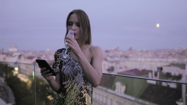 caucasian woman in cocktail dress on rooftop drinking champagne and checking smart phone - cocktail dress stock videos & royalty-free footage