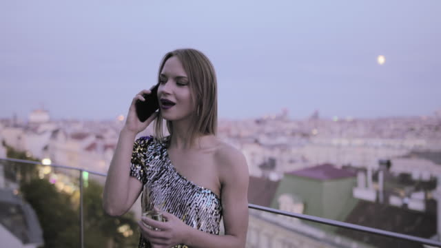 caucasian woman in cocktail dress on rooftop drinking champagne and talking on smart phone - cocktail dress stock videos & royalty-free footage