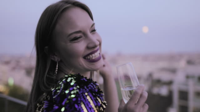 caucasian woman in cocktail dress on rooftop drinking champagne at party - cocktail dress stock videos & royalty-free footage