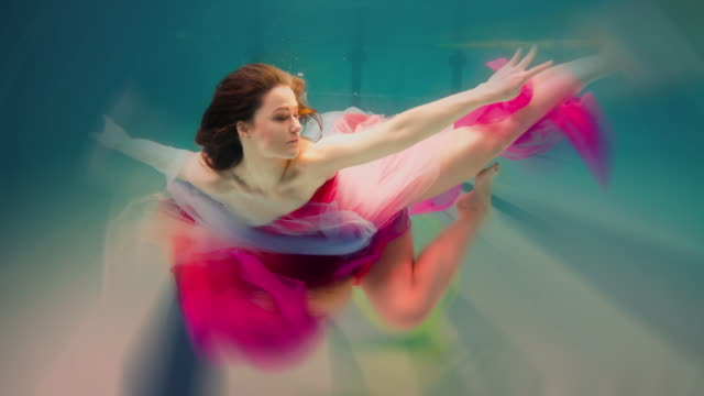 caucasian woman in dress swimming under water - femininity stock videos and b-roll footage
