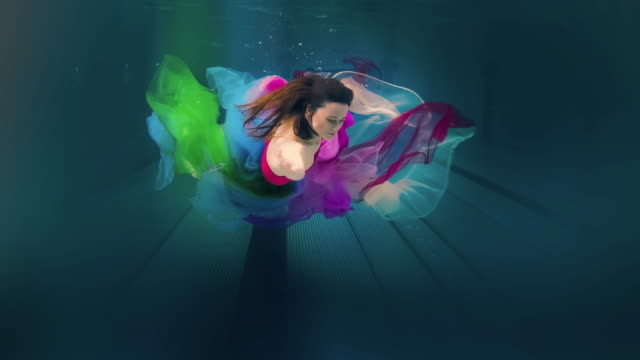 caucasian woman in dress swimming under water - ethereal stock videos and b-roll footage